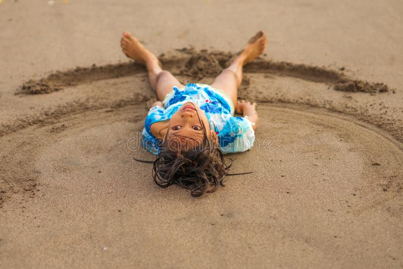 Beach lifestyle portrait of young beautiful and happy Asian American mixed ethnicity child girl 7 or 8 years old playing lying on royalty free stock image