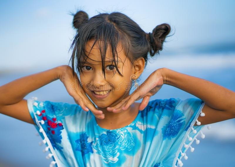 Beach lifestyle portrait of young beautiful and happy Asian child girl 8 or 9 years old with cute double buns hair style playing royalty free stock photography