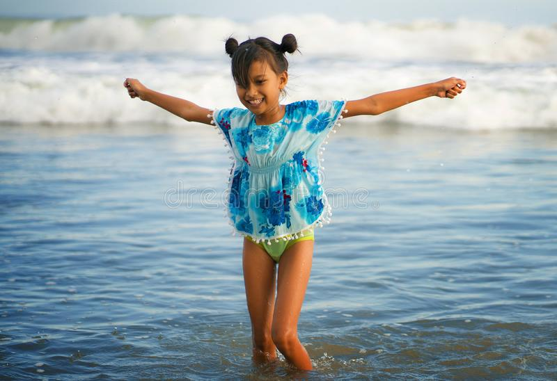 Beach lifestyle portrait of young beautiful and happy Asian child girl 8 or 9 years old with cute double buns hair style playing stock image