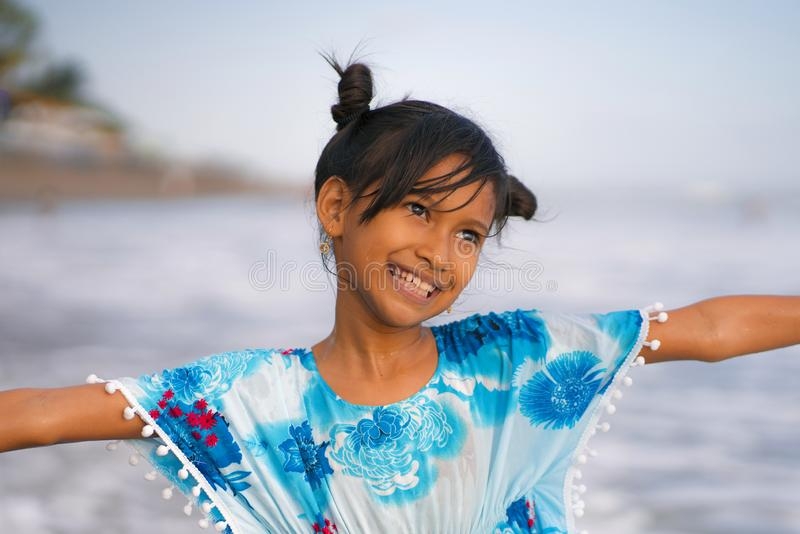 Beach lifestyle portrait of young beautiful and happy Asian child girl 8 or 9 years old with cute double buns hair style playing stock images