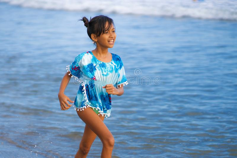 Beach lifestyle portrait of young beautiful and happy Asian child girl 8 or 9 years old with cute double buns hair style playing royalty free stock image