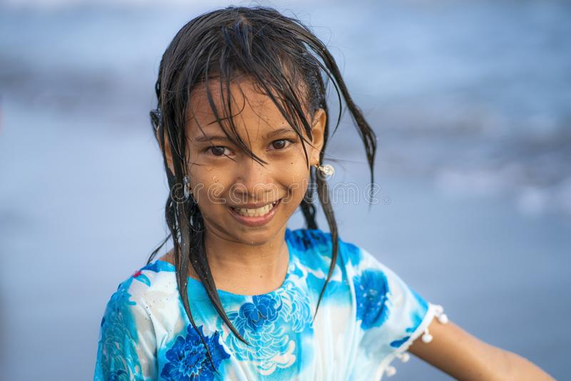 Beach lifestyle portrait of young beautiful and happy 7 or 8 years old Asian American mixed child girl with wet hair enjoying royalty free stock photography