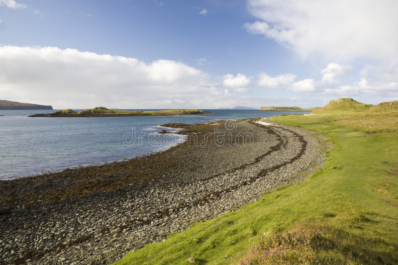 Beach line with blue sky, clouds and green grass royalty free stock photos