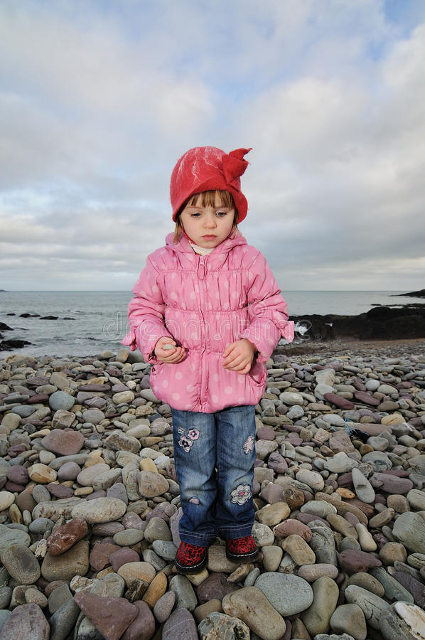 At the Beach. A little girl at the beach on a cold day royalty free stock photo