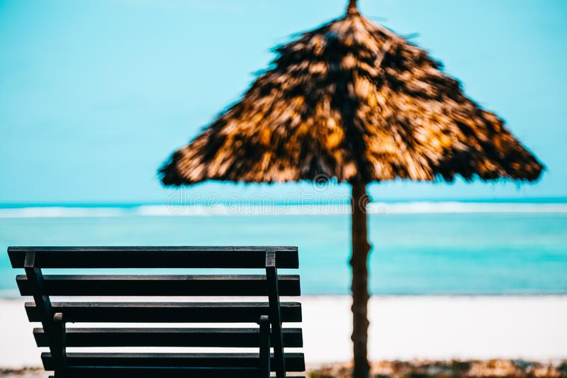 Beach Lounge Chair With Straw Parasol stock photography