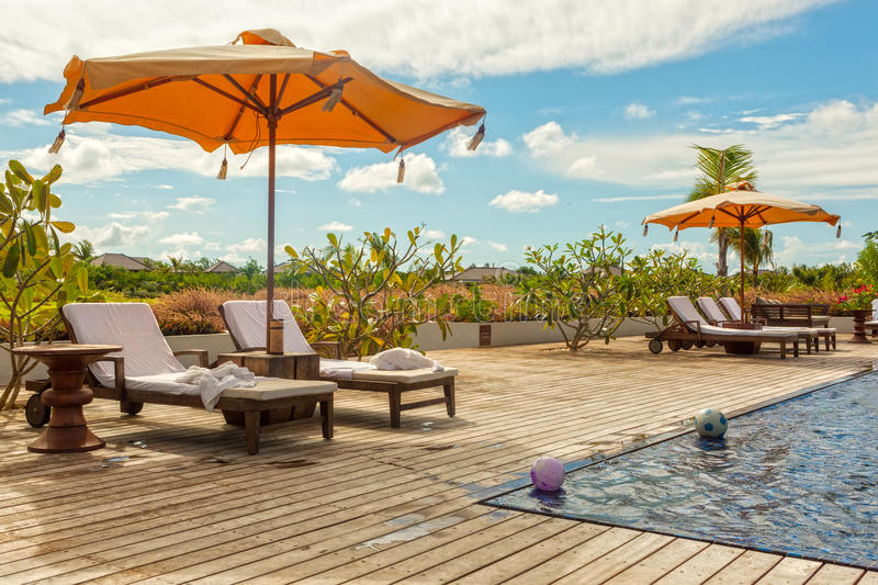 download beach lounge chairs with towels under umbrella at the poolside o royalty free stock photos