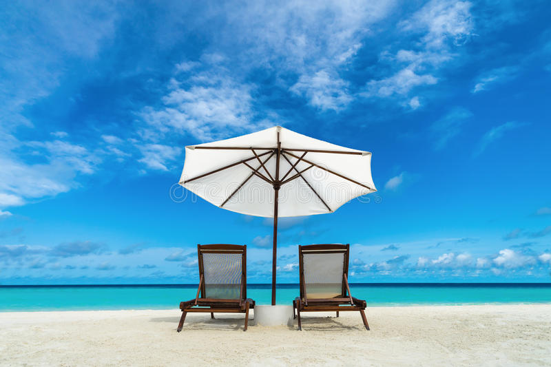 Beach lounger and umbrella on sand beach. Concept for rest, relaxation, holidays, spa, resort. Beach lounger and umbrella on sand beach. Concept for rest royalty free stock images