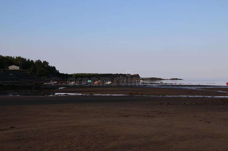A beach at low tide with a number of boats moored on what is now dry ground stock photo