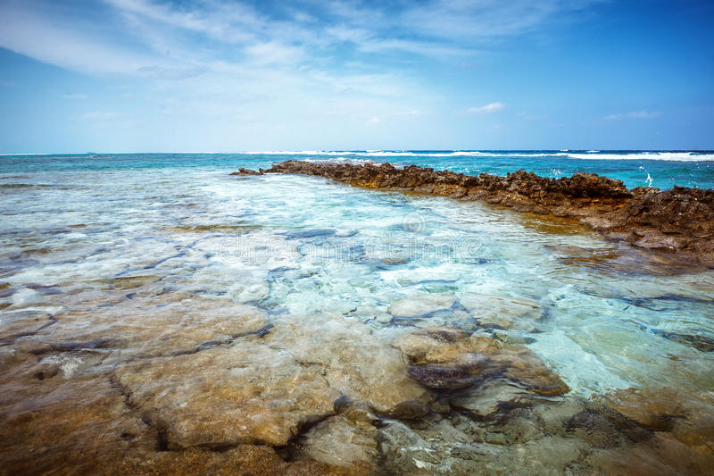 Beach at Maldives island Fulhadhoo with white sandy beach and sea and stones and rocks, corals. Scenic view of Wild idyllic Beach at Maldives island Fulhadhoo royalty free stock photography