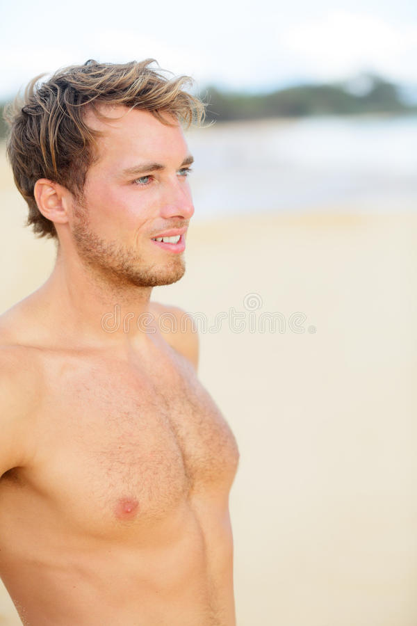 Beach man looking at ocean stock photo