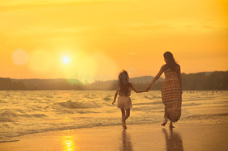 On the beach. Mother and daughter walking on the beach with sunset royalty free stock photo