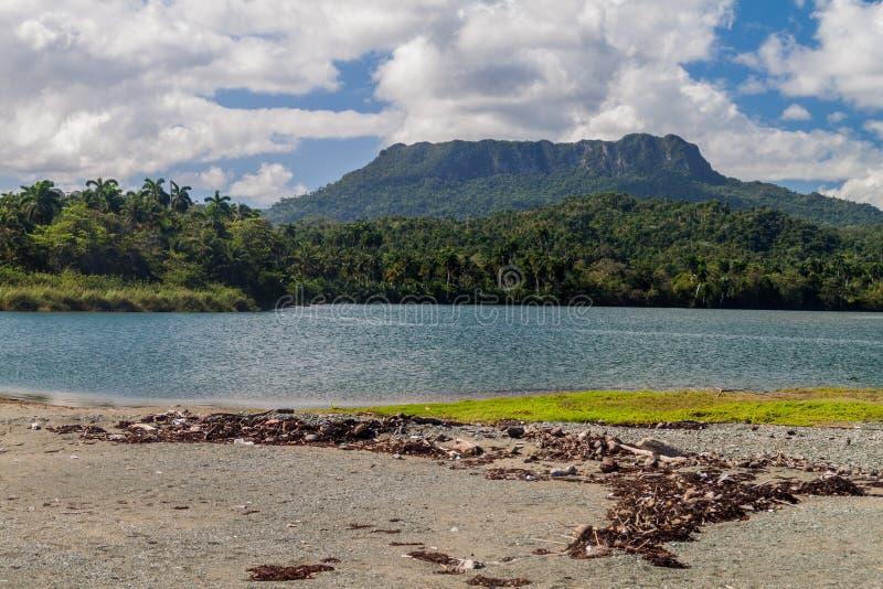 Beach at the mouth of Rio Toa river near Baracoa, Cuba. El Yunque mountain in the backgroun royalty free stock photos