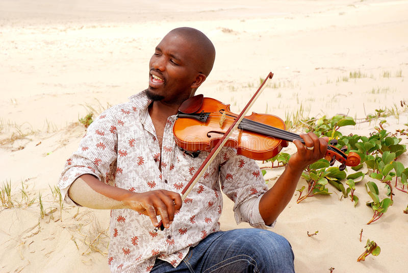 Beach musician portrait. An African American beach musician playing his violin and singing while sitting in the sand royalty free stock photos