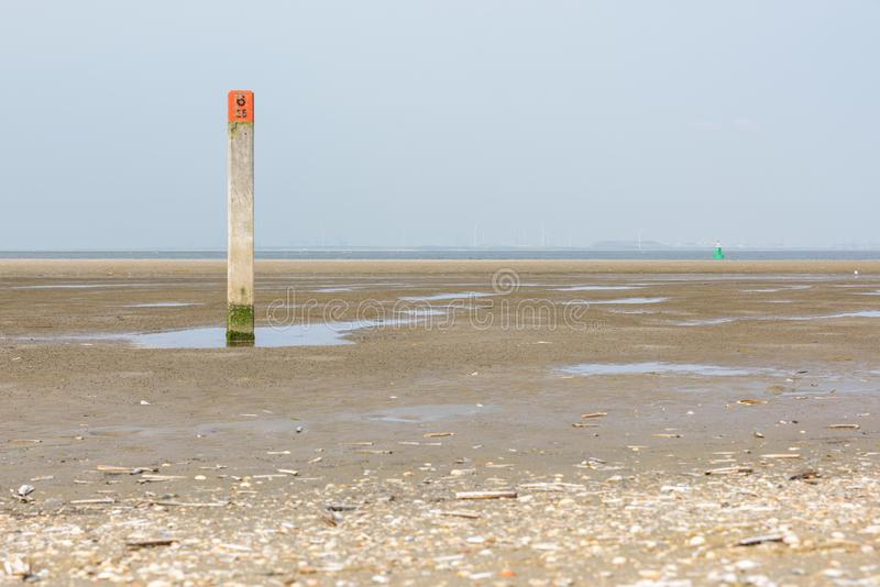 A wooden pole with red head on the beach of the North Sea in the Netherlands stock images