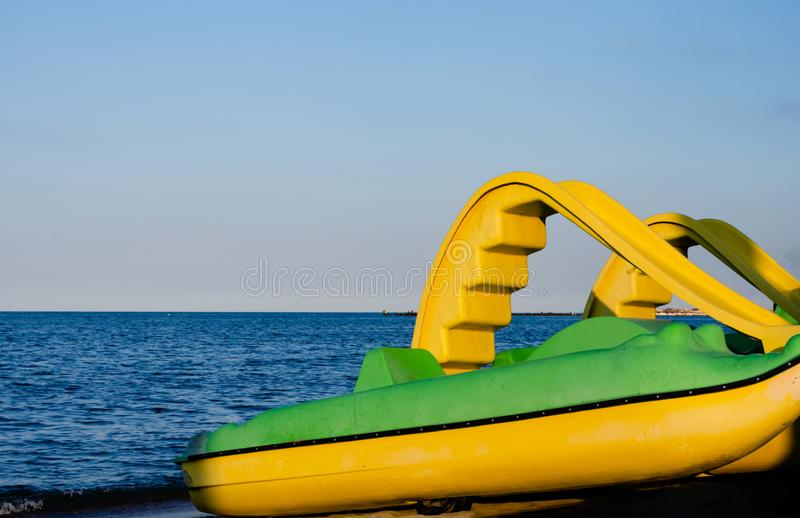 Paddle yellow boats during summer season parked by the seashore ready to  be rent for fun stock image