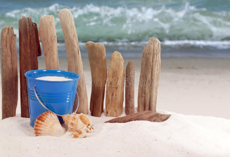 Beach Pail. Bright blue beach pail filled with sand in front of rustic driftwood fence and ocean wave in background royalty free stock photo