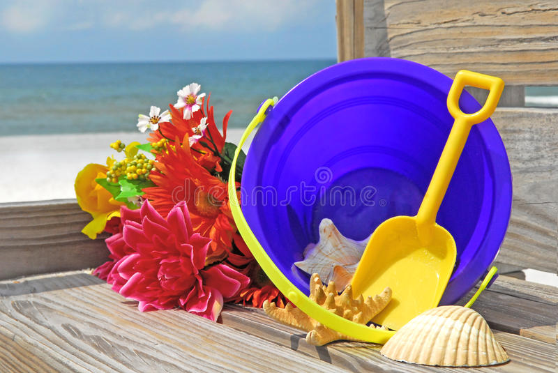 Beach pail and flowers. Beach sand pail and flowers on boardwalk at ocean royalty free stock images