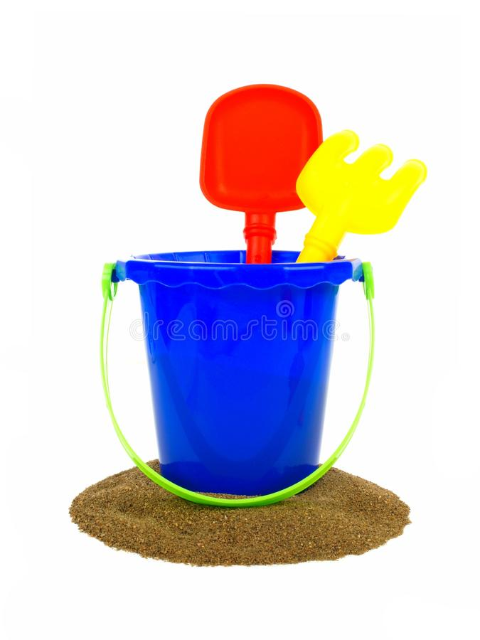 Beach pail with sand. Toy sand pail with shovel and rake over a white background royalty free stock photos