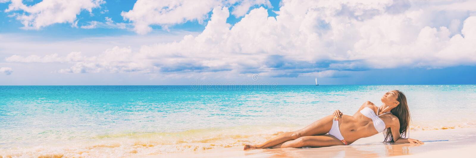 Beach paradise sexy bikini woman lying down on sand relaxing sun tanning in tropical caribbean travel destination for. Summer vacation. Panoramic banner stock photo