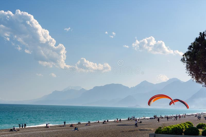Beach on the beach with paragliders on the background of mountains royalty free stock photos