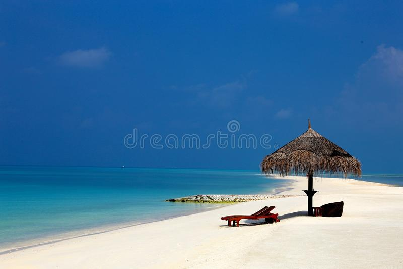 Beach with a parasol stock photos