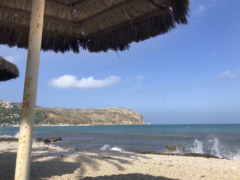 Beach Parasol på persikostranden nära Javea, Spanien royaltyfri foto