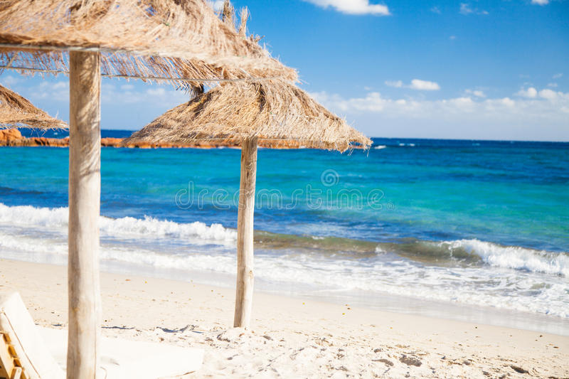 Beach Parasols in Corsica. Straw parasols on a beach on corsica`s eastern coast stock image