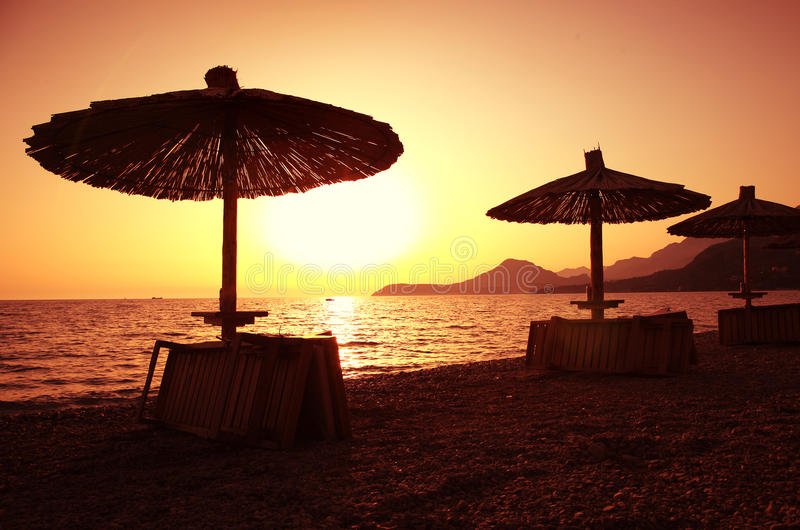 Beach parasols at sunset. Beautiful beach with deck chairs and parasol at sunset stock images
