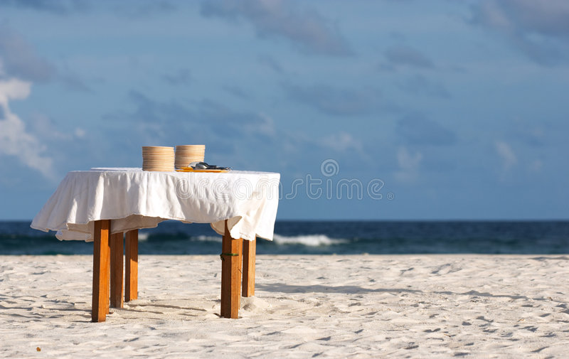 Beach party. Table with many plates prepared for beach party close to the shore royalty free stock photography