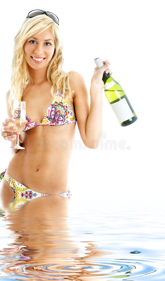 Beach party girl in water. Beach party girl in colorful bikini with glass and bottle of wine royalty free stock photos