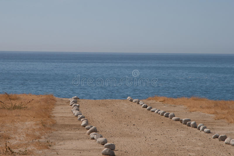 Stone lined path on beach royalty free stock photos