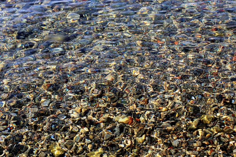 Beach pebbles under transparent sea water surface royalty free stock images