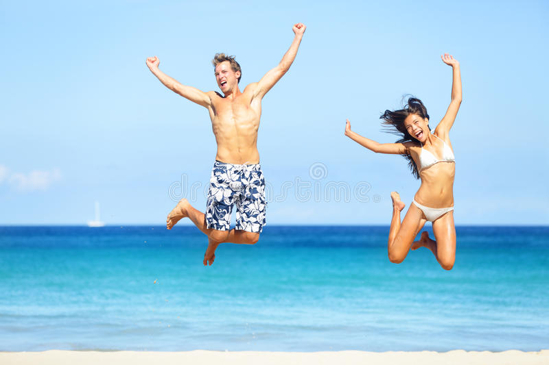 Beach people - happy couple jumping stock images