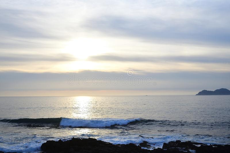 Sunset on the beach. Clouds on the horizon with a calm sea,. Beach photographed at sunset. Clouds on the horizon with a calm sea, breaking the waves on the rock royalty free stock photos