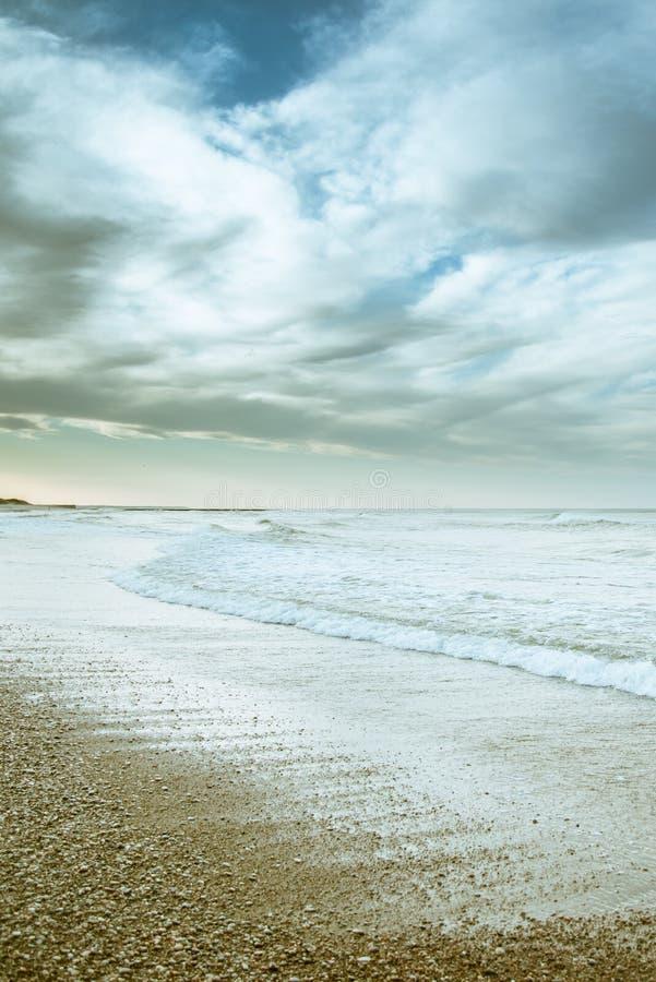 Beach photography - blue ocean waves, sand, overcast sky. Clouds royalty free stock photography
