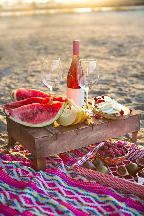 Beach picnic with rose wine, fruits, nuts meat and cheese. Outdoor picnic with rose wine, fruits, nuts meat and cheese stock photo