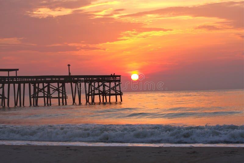 Beach with pier at sunrise. Ocean view of beach with pier at sunrise stock image