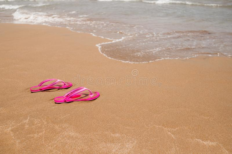 Beach pink flip-flops on a light sand. Texture of light sand. The concept of a beach holiday. Summer concept. Flat lay, side view royalty free stock images