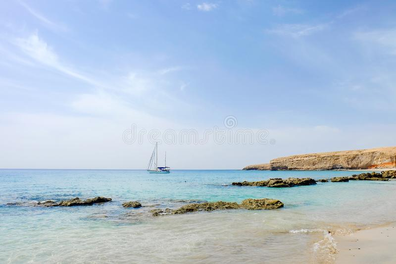 Beach Playa las Coloradas in Morro Jable on Fuerteventura, Spain. Viw on a sailboat and the beach Playa las Coloradas in Morro Jable on the Canary Island royalty free stock images