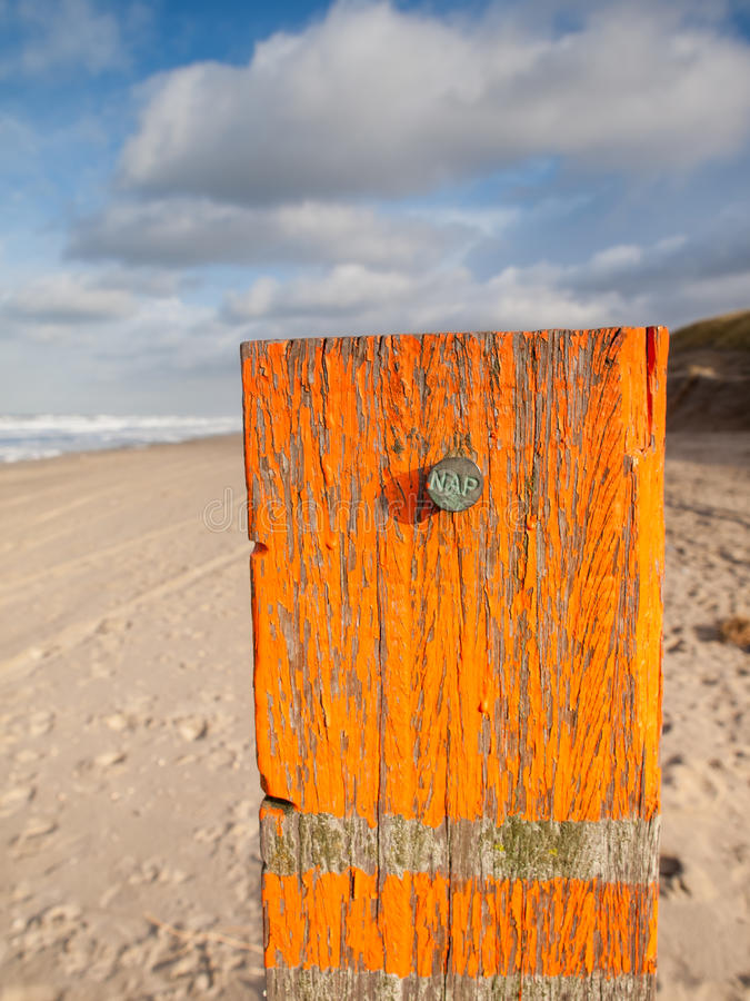 Beach post with sea level marker with beach and sea behind. Beach post with orange flaking paint carrying a metal marker nail indicating the dutch standard sea royalty free stock image