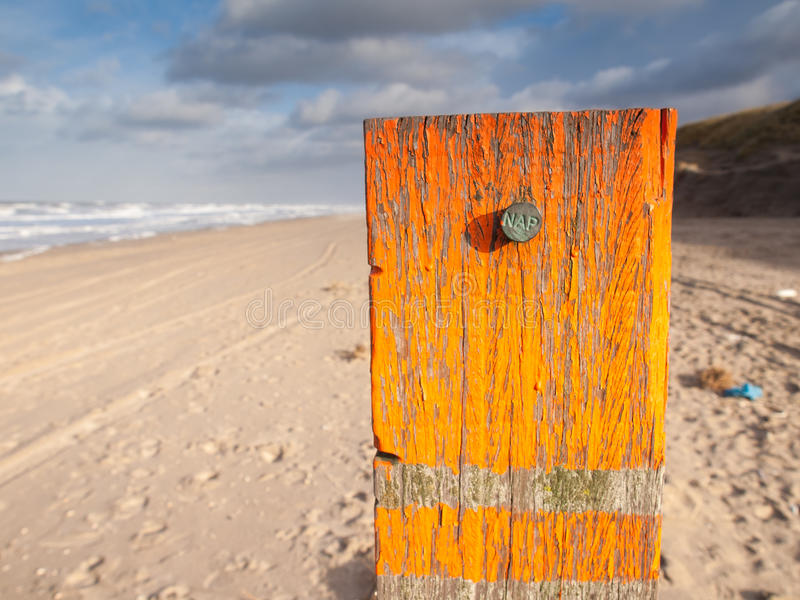Beach post with sea level marker. Beach post with orange flaking paint carrying a metal marker nail indicating the dutch standard sea level datum point the stock photography