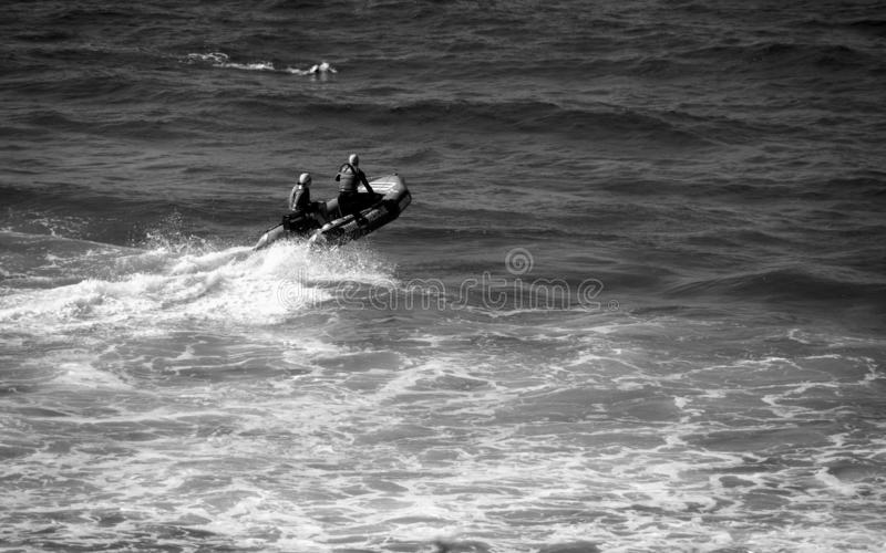 Beach rangers on a red rescue boat a surfer swimming nearby monochrome. Monochrome picture of beach life guards splashing waves and rushing to a surfer swimming royalty free stock image