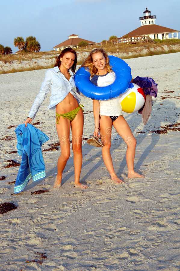 Beach ready. Two smiling teenage girls at the beach with toys