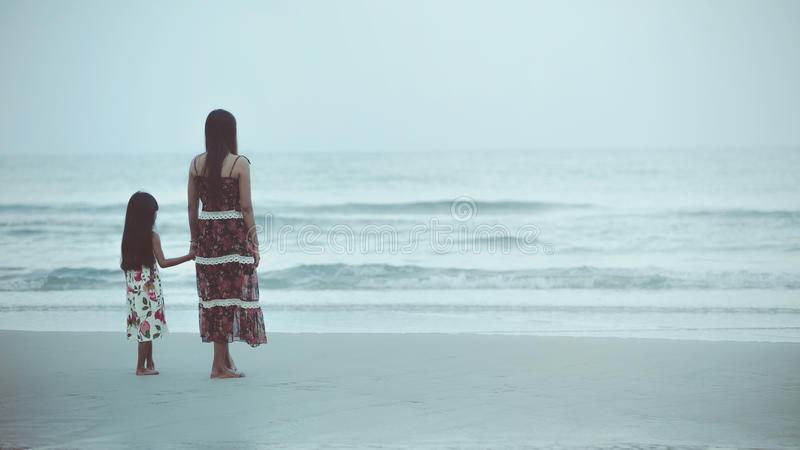 The beach. Rear view of a mother and daughter standing on the beach, Vintage colour tone royalty free stock images