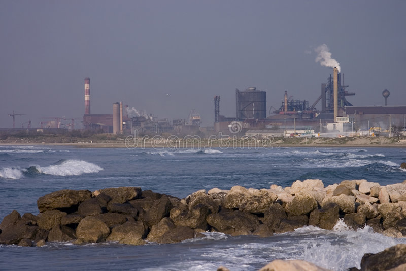 Beach refinery. Oil refinery in the south of France, rocky beach, rough sea and a dark brooding sky royalty free stock images