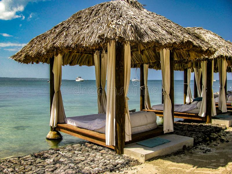 Beach Relaxation Hideaway Bungalow Hut. Blue skies, blue waters, relaxation bungalows and silky soft sand eases tensions and forces you to become one with nature royalty free stock images