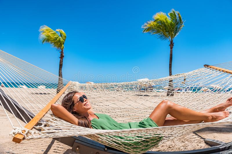 Beach relaxation sun tanning girl lying down on hammock relaxing sunbathing in Caribbean vacation holiday at resort hotel. Happy stock photos