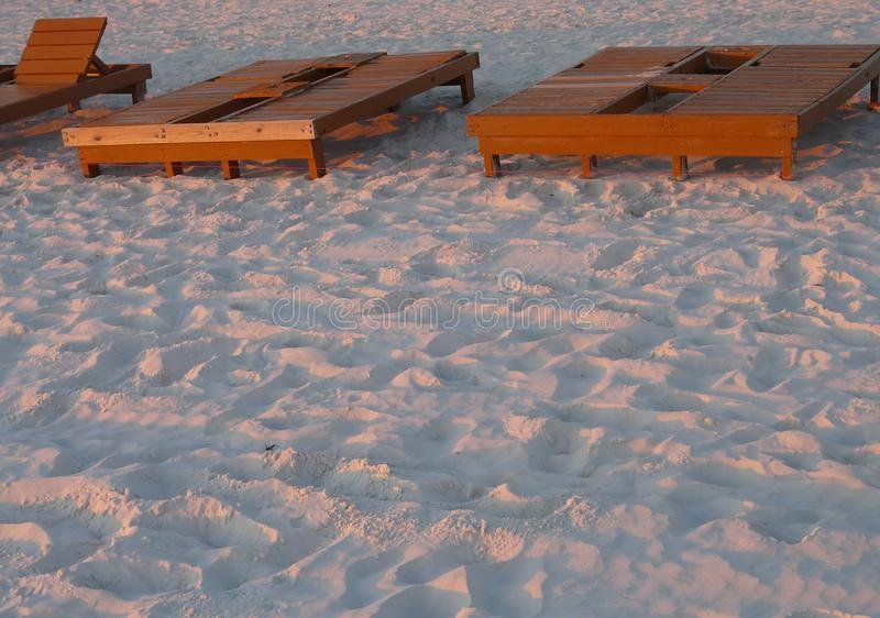 Beach Rental Lounge Chairs at Sunset. The sun setting on beach chairs for rent at Panama City Beach, Florida, gives the sand a pink tinge stock photos