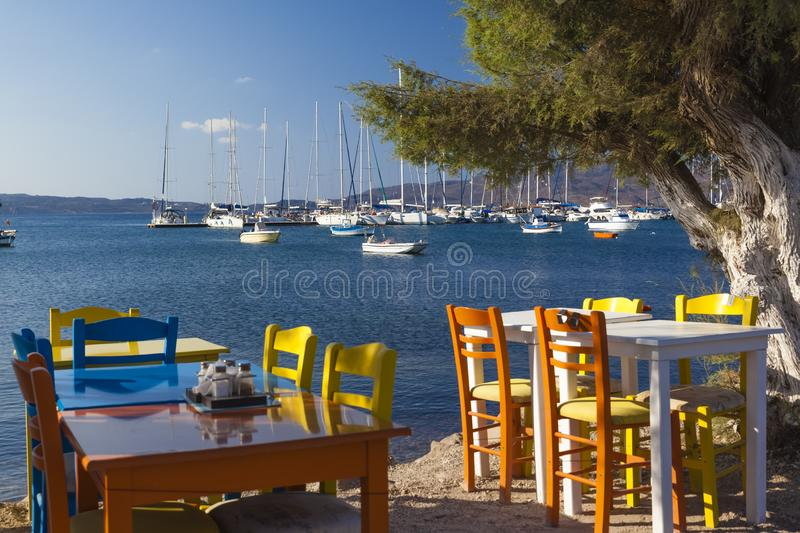 Beach restaurant with colourful chairs at the shore of Adamis, Milos, Greece stock photography