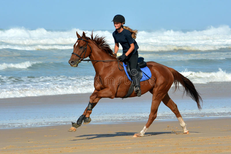 Beach ride fun. A beautiful teenage Caucasian female rider with happy smiling facial expression galloping on her chestnut horse on the beach close to the sea